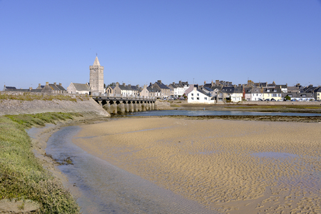 Beach and town icts with church of Our Lady of Port-Bail gold Porbail, a town in the peninsula of Cotentin in the Manche department in Lower Normandy in north-western France
