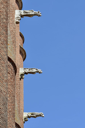gargoyles: Three gargoyles on the blue sky background, of the Sainte Cecile cathedral made in red bricks at Albi in southern France, Midi Pyrenees Region, Tarn department