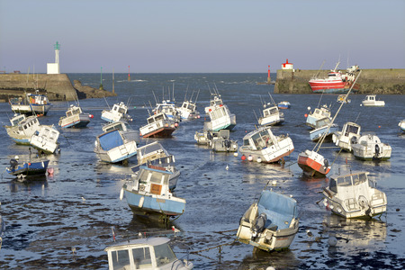 manche: Boats at low tide and lighthouse in the harbor of Barfleur, a town in the peninsula of Cotentin in the Manche department in Lower Normandy in north-western France