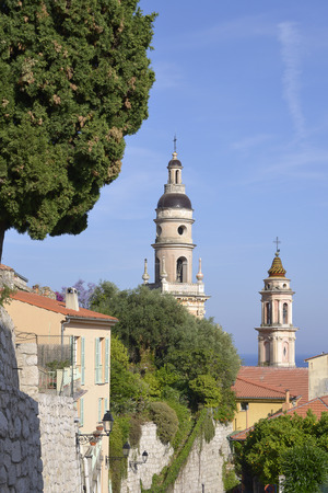 maritimes: Baroque Basilica of St. Michael the Archangel and trees at Menton, a town in the Alpes-Maritimes department in the Provence-Alpes-Cote of Azur Region in southeastern France.