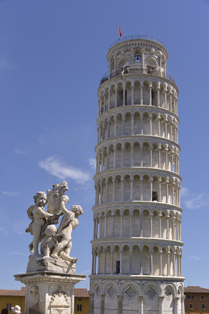 empties: Cherubim the statue of the fountain dei putti with the famous leaning Tower of Pisa (Torre pendente di Pisa in Italian) is a city in Tuscany, central Italy, straddling the River Arno just before it empties into the Tyrrhenian Sea Stock Photo