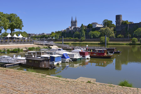 west river: Port on the Maine river of Angers and the cathedral Saint Maurice and castle at the top of hill. Angers is a commune in the Maine-et-Loire department, Pays de la Loire Region, in western France about 300 km (190 mi) south-west of Paris Stock Photo