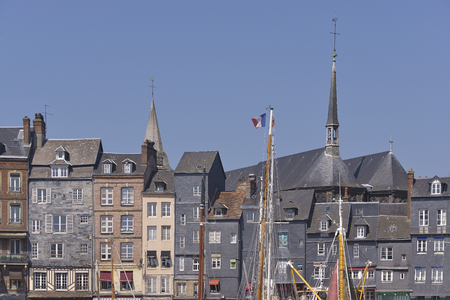 Facades of building and the Sainte-Catherine church with boat mast at Honfleur, commune in the Calvados department in the lower Normandy region in northwestern France