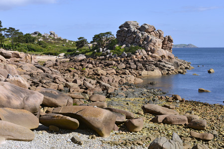 ploumanach: Famous Pink Granite Coast of Ploumanach with islands Monks and Bono in the background. Ploumanach is a village in the commune of Perros-Guirec. It is found in the region Brittany in the Cotes dArmor department in the west of France. Stock Photo