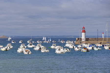 Port and lighthouse at high tide of Erquy, a commune in the Cotes of Armor department of Brittany in northwestern France on the coast of Penthievre. Stock Photo