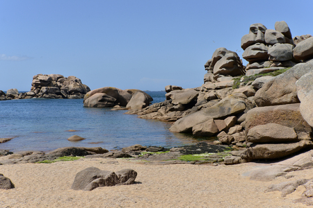 Beach and famous pink granite rocks on the coast at Ploumanach, village in the commune of Perros-Guirec. It is found in the region Brittany in the Cotes dArmor department in the west of France. Stock Photo
