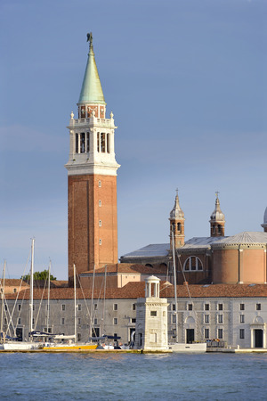 Bell tower of the Basilica of San Giorgio Maggiore and the port in Venice, a famous city in northeastern Italy and the capital of the Veneto region.