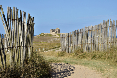 Path in the dunes of Quiberon in France and the ruins of the house of the Customs officer in the background. The Morbihan department in Brittany in north-western France Stock Photo