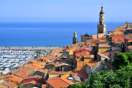 View of the town of Menton with the port and Basilica of Saint Michael the Archangel. Menton is a commune in the Alpes-Maritimes department in the Provence-Alpes-Cote d'Azur region in southeastern France.