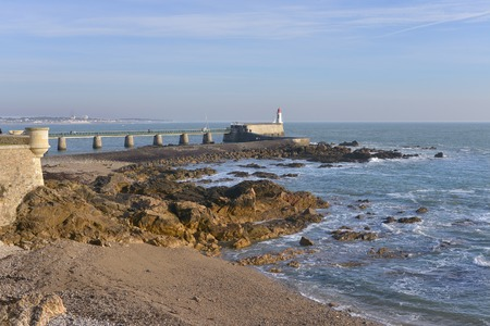 Rocky coastline and lighthouse at Les Sables d'Olonne, commune in the Vend?e department in the Pays de la Loire region in western France