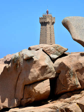 Mean Ruz lighthouse on the famous Pink Granite Coast (côte de granite rose in french) behind big rocks at Ploumanac'h, village in the commune of Perros-Guirec in France