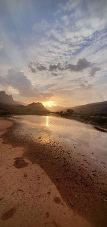 Sunset view with sun reflection in water pools after rain, Sultanate of Oman Banque d'images