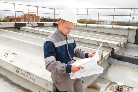 the builder looks at the drawings of the building under construction