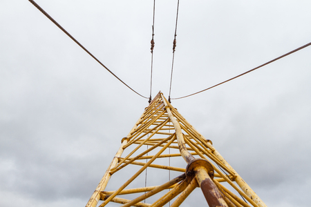 The arrow of an old yellow crane at a tremendous height against the sky