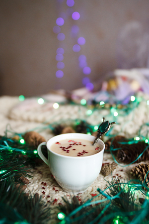 A cup of coffee with ornaments in the form of stars, fir branches, pine cones and blue garland