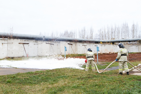 Firefighters extinguish the fire with a chemical foam coming from the fire engine through a long hose Stock Photo