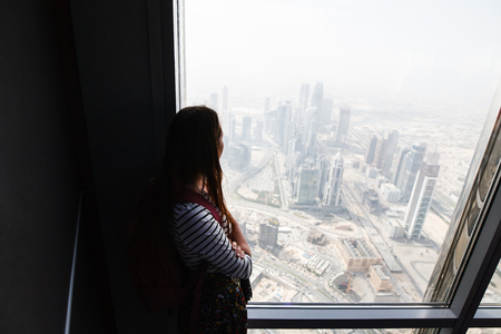 A girl looks from a tall building through a panoramic window to a big city Reklamní fotografie