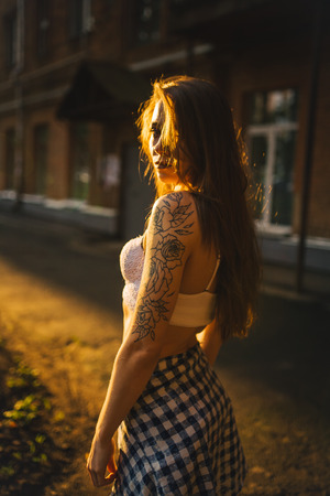A girl with a tattoo in a white top and sweatpants poses against the background of the dawn and the building. Urban Style. Girl in a white top and sweatpants. Stock Photo
