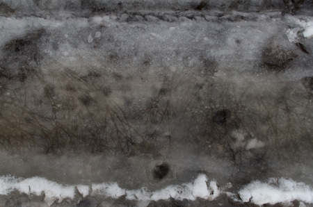 Winter melting snow dark gray background reflection in water Stock Photo