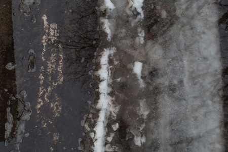 Groung melting snow dark gray puddle