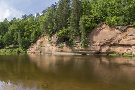 Sandstone cliffs Velnala by the river in Gauja national park in Latvia Stock Photo