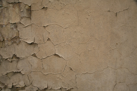 Texture of old cracked painted peeling beige brown wall background