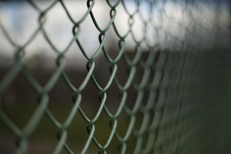 Green dark mesh fence closeup urban background Stock Photo