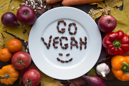 White plate with various vegetables and go vegan text top view Stock Photo - 89216531
