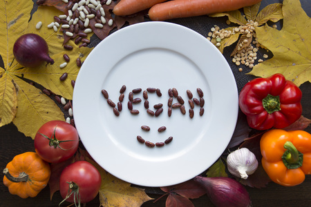 White plate with various vegetables and happy vegan top view