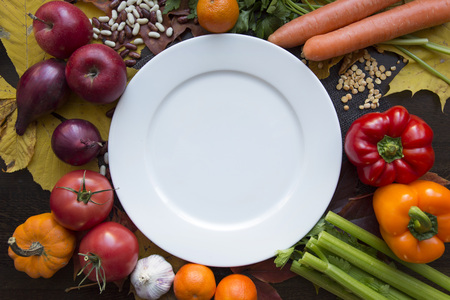 White empty plate with various vegetables top view
