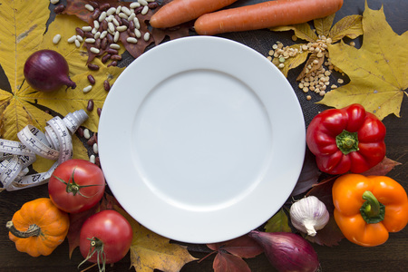 White emty plate with measuring tape and vegetables top view Stock Photo