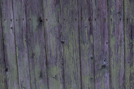 Beautiful old green purple gray wooden fence with peeling paint texture background close-up Stock Photo