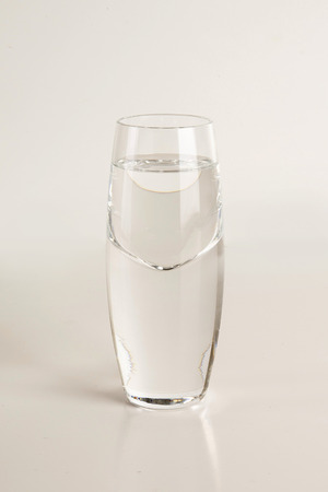 Glass of vodka on light gray background Stock Photo