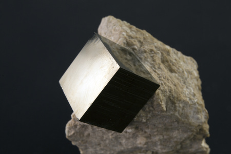 Shiny smooth crystal of pyrite in the form of a cube on a dark background