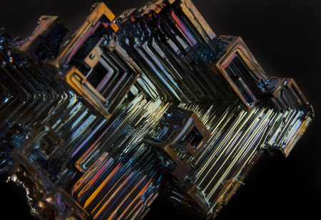 Shiny colorful mineral bismuth on a dark background