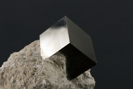 Shiny smooth crystal of pyrite in the form of a cube on a dark background Stock Photo - 95456488