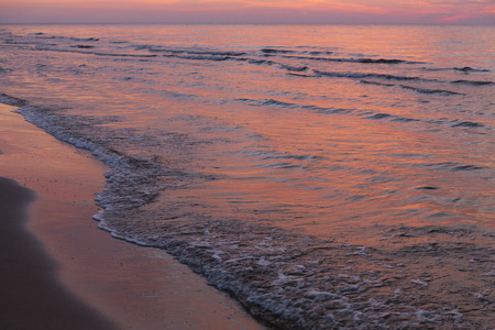 Colorful sunset waves on sandy Baltic beach in autumn late evening