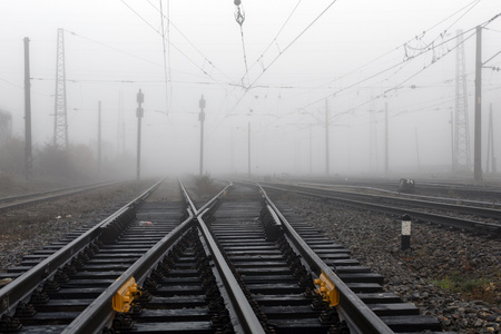 Crossing railways  fading away disappearing in the mist in autumn morning Stock Photo