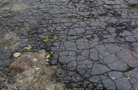 Old aged grey cracked asphalt road surface