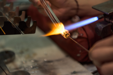 glass artist melting a glass pearl with a torch in Murano Venice