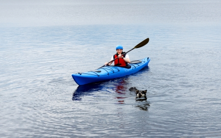 Young man riding around lake on kayak  Sports and recreation photo