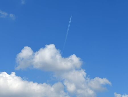 Heavenly landscape with plane in distance and cumulus clouds