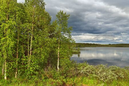 Picturesque northern forest lake with reflection of clouds in cold water in Finnish Lapland. Kuusamo Banco de Imagens