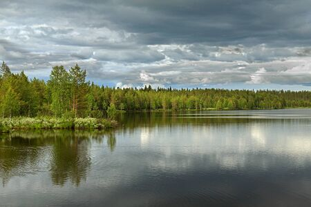 Northern forest lake in gloomy weather. Finnish Lapland