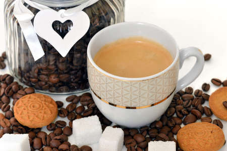 Cup of espresso with white sugar and cookies on background of jar with coffee grains