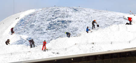 Zaryadye Nature Landscape Park in frosty snowy winter. Team of workers-climbers clean glass canopy from snowdrifts