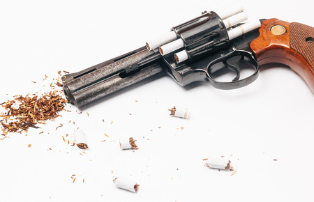 killing cancer: Revolver loaded with cigarettes to symbolize the dangers of smoking Stock Photo