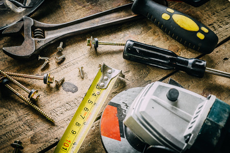 carpenter items: Different tools on a wooden background.