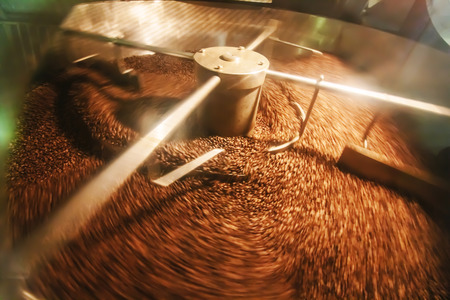 Roaster: The freshly roasted coffee beans from a coffee roaster being poured into the cooling cylinder. Frozen moment Stock Photo