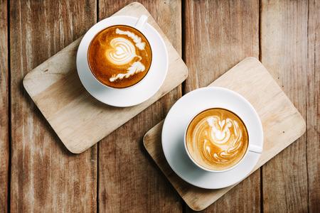 나무 테이블에 뜨거운 라떼 아트 커피의 선택적 초점 컵, 하얀 거품에 초점